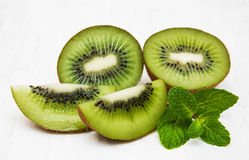 Kiwi fruit. With mint on a old white wooden background Royalty Free Stock Photo