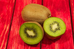 Kiwi fruit. A photo shows kiwi fruit placed on a red made from a wooden background. Some of the fruits are crossed showing juicy flesh and black pips Royalty Free Stock Image