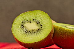Kiwi fruit. A photo shows kiwi fruit placed on a red made from a wooden background. Some of the fruits are crossed showing juicy flesh and black pips Stock Images