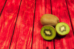 Kiwi fruit. A photo shows kiwi fruit placed on a red made from a wooden background. Some of the fruits are crossed showing juicy flesh and black pips Royalty Free Stock Photos