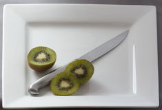 Kiwi fruit on a plate. Kiwi fruit cut and plated with a knife Stock Photos