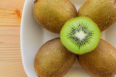 Kiwi fruit on a plate. Whole kiwi on a plate, and one cut Stock Photo