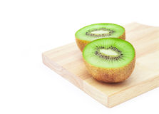 Kiwi fruit slice on wooden chopping board in white background Royalty Free Stock Image