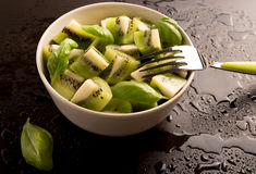 Kiwi fruit sliced segments with basil leaves and fork in a round bowl Stock Photos