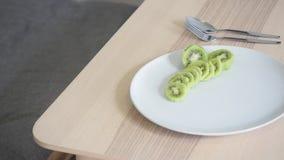 Kiwi Fruit Slices en el plato blanco en la tabla y los cubiertos de madera por otra parte almacen de metraje de vídeo