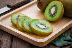 Kiwi fruit slices on wooden plate Royalty Free Stock Photo