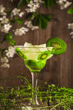 Kiwi fruit soft drink cocktail with ice on a wooden background and flowers Royalty Free Stock Photos