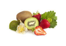 Kiwi fruit and strawberries. Kiwi fruit with leaf and blossoms and fresh strawberries isolated on white stock image