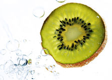 Kiwi Fruit in Water. Kiwi Fruit slice in clear water, isolated on white. Lit from below Stock Photography