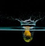 Kiwi fruit into water, isolated on black Royalty Free Stock Photos