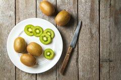 KIwi fruit on white dish and  knife on wooden background. Royalty Free Stock Images