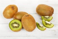 Kiwi fruit. Whole and sliced kiwi fruit on white wooden planks Royalty Free Stock Photos