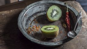 Kiwi fruit on wooden surface. Split up kiwi fruit on wooden surface with weathered copper bowl on black background Stock Photo