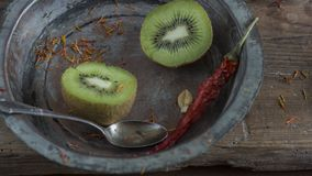 Kiwi fruit on wooden surface. Split up kiwi fruit on wooden surface with weathered copper bowl on black background Stock Photography