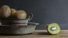 Kiwi fruit on wooden surface. Split up kiwi fruit on wooden surface with weathered copper bowl on black background Royalty Free Stock Images