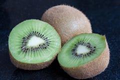 Kiwi Fruits. Two kiwi fruits, one halved, against a black granite background Stock Photography