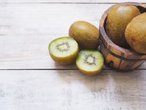 Kiwi fruits and barrel bucket on white wooden background. Stock Photo