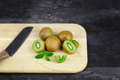 Kiwi fruits on a cutting desk. Tropical cut and whole kiwis with a knife on a black table background. Healthy fruits. A view from above on a wooden cutting desk stock photography