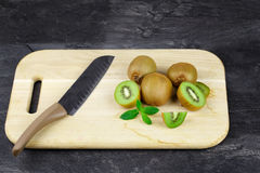 Kiwi fruits on a cutting desk. Tropical cut and whole kiwis with a knife on a black table background. Healthy fruits. royalty free stock photo