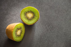 Kiwi fruits on a dark stone table with place for the text Stock Photography