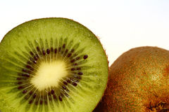 Kiwi Fruits. A kiwi fruit cut in half, showing the juicy flesh and pips and the fuzzy skin Stock Image