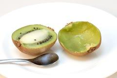 Kiwi geschnitten, eine der Hälfte gegessen Stockfoto