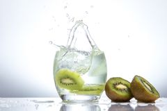 Kiwi in a glass and splashes of water. Tasty and healthy food. Seasonal drinks .Summertime.Green freshness Stock Photo