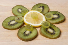 Kiwi, grapes and lemon on wooden brown background. Stock Images
