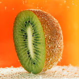 Kiwi half  in soda water. Half of kiwi with bubbles in soda water Stock Photography