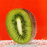 Kiwi half  in soda water. Half of kiwi with bubbles in soda water Royalty Free Stock Photo