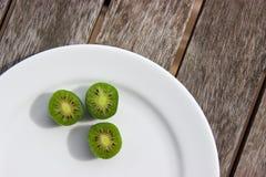 Kiwi jagody na bielu talerzu na drewnianym stole (arktyczny kiwifruit) Obrazy Stock