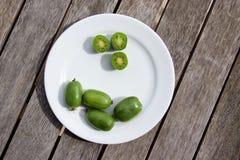 Kiwi jagody na bielu talerzu na drewnianym stole (arktyczny kiwifruit) Zdjęcie Royalty Free