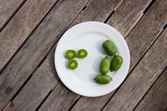 Kiwi jagody na bielu talerzu na drewnianym stole (arktyczny kiwifruit) Obraz Royalty Free