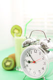 Kiwi juice in a glass and alarm clock Stock Photo