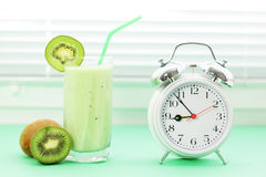 Kiwi juice in a glass and alarm clock Royalty Free Stock Photography