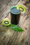 Kiwi juice. In a green and wooden background Stock Photos