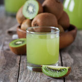 Kiwi juice. Sweet fresh juice with kiwi on the wooden table, selective focus and square image Stock Image
