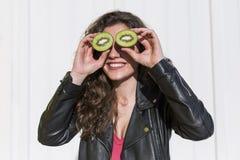 Kiwi Kiwi divertente della tenuta della donna della frutta sana per lei occhi Fotografia Stock