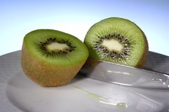 Kiwi with knife. Kiwi in the foreground cut in two with knife Stock Images
