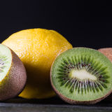 Kiwi and lemon on black wooden table, dark background, room for Royalty Free Stock Image