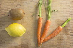 Kiwi lemon and carrots on a wooden background Royalty Free Stock Image