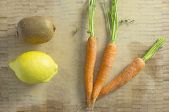 Kiwi lemon and carrots on a wooden background Royalty Free Stock Photos