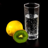 Kiwi, lemon and a glass of mineral water Stock Photos