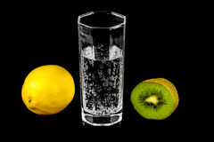 Kiwi, lemon and a glass of mineral water Stock Images