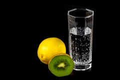 Kiwi, lemon and a glass of mineral water Stock Image