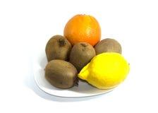 Kiwi, lemon and orange, on a white plate, a side view Royalty Free Stock Photos