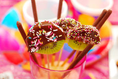 Kiwi lollipops poured chocolate. With colorful sprinkles on birthday party for children Stock Photo