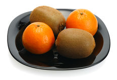 Kiwi and mandarin on a black plate Royalty Free Stock Photos