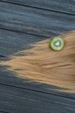 Kiwi och hår på trätabellen Fotografering för Bildbyråer