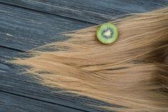 Kiwi och hår på trätabellen Royaltyfria Foton